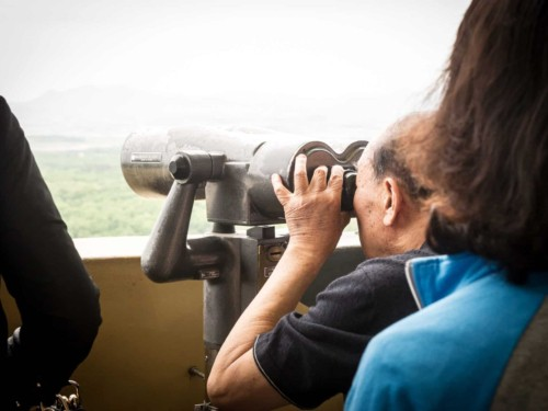 A man at Dora mountain observatory on a half day DMZ tour looking at North Korea through a telescope
