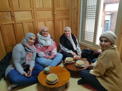 네명의 방문객이 전통 한옥 스타일의 찻집에서 쉬고 있습니다.