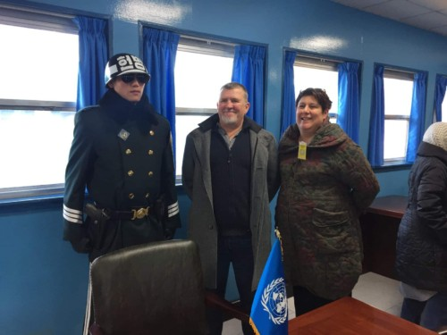People taking a picture with a border guard inside the UN conference building during a JSA tour