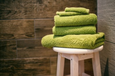 Green towels on top of a stool in a traditional sauna