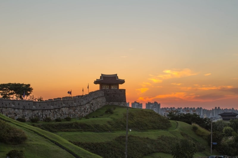Suwon's Hwaseong Fortress with an orange sky in the background