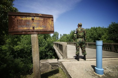 A soldier standing guard in front of the Bridge of No Return facing North