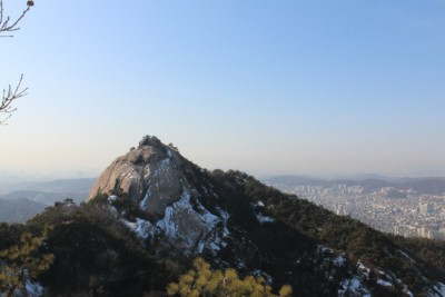 A view of Seoul can be seen from behind a jagged rock face in Bukhansan