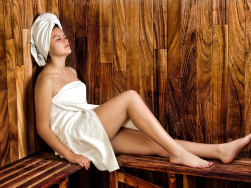 A woman wrapped in a white towel lying down and relaxing in a hot sauna
