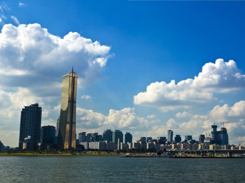 Looking at the gold colored 63 Building located on Yeouido Hangang Park from across the Han River