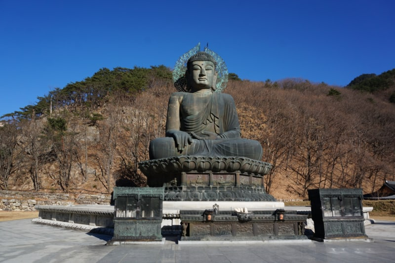 A giant Buddha statue nearby Shinheungsa temple with leaf-less trees in the background