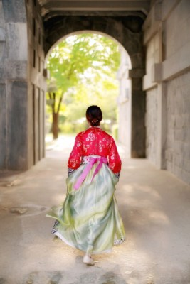 Girl dressed in a Hanbok walking through a palace gate