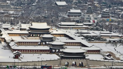 A view of Gyeongbok Palace from above covered in white snow during winter in Seoul