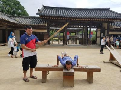 조선시대의 처벌 중 하나를 체험하는 두 명의 관광객