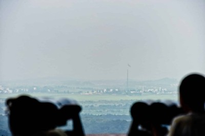 Tourists looking at Kijong dong North Korea's propaganda village from Dora Observatory located very close to the North-South DMZ border