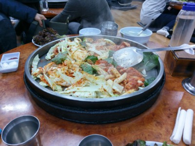 Steam coming off of a delicious Korean Dak-Galbi dish which is being cooked on the table in front of customers