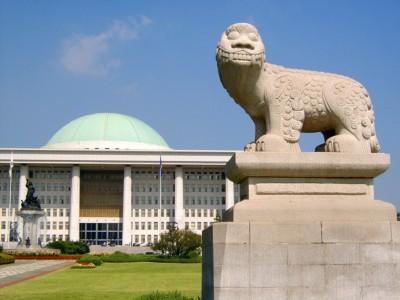 The Korean National Assembly Building in Seoul with a statue infront and unique round blue roof