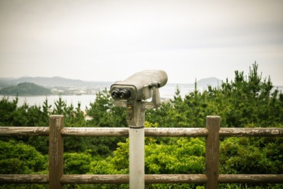 An observation deck with a pair of high-powered binoculars on the peak of one of Jeju's mountains