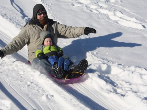 Father and son having fun snow sledding together