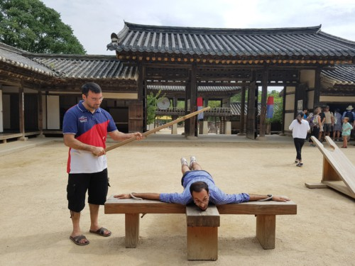 Two men experiencing what traditional punishment was like at the Korean Folk Village in Yongin