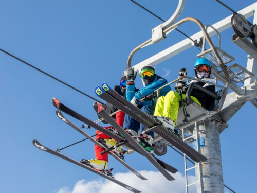People riding a ski lift to the top of the mountain