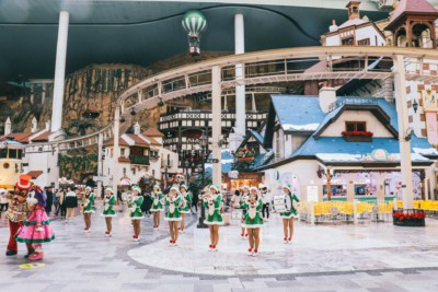 Ladies dressed in green Christmas outfits and hats playing band instruments inside Lotte World in Seoul