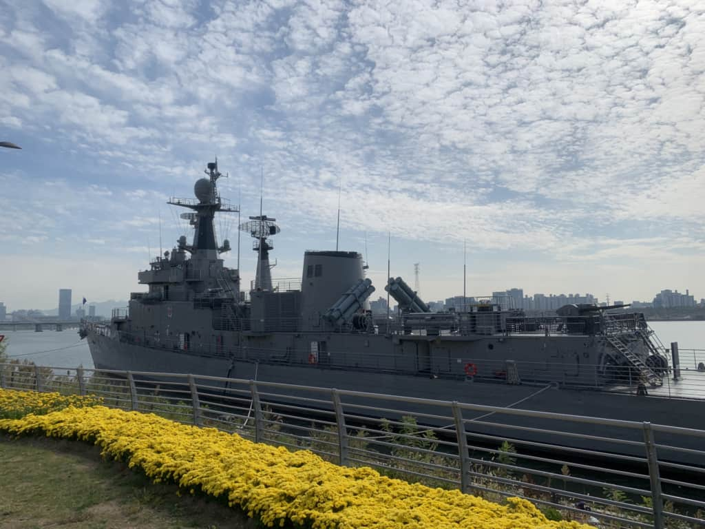 A photo of Seoul Battleship Park situated alonside the beautiful Han River with clear blue skies above